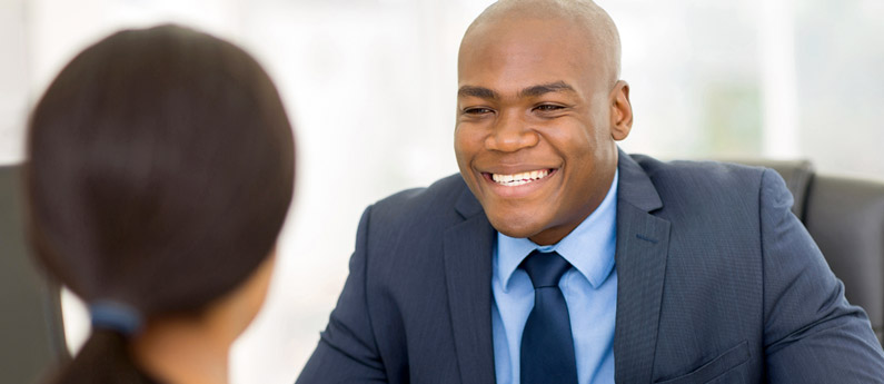 Male Bredin College Admissions Advisor helping female prospective student in an office, both are smiling