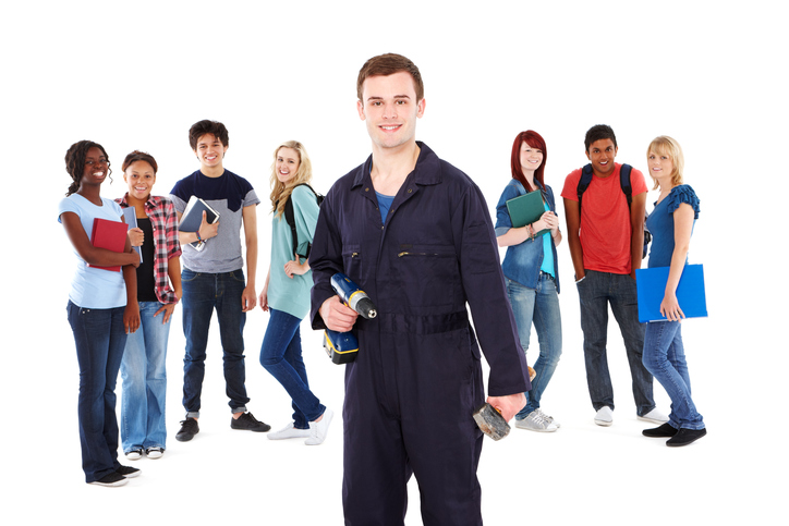 Young handyman poses in coveralls while students stand in the background. Horizontal shot. Isolated on white.