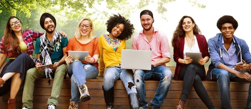 A group of multiracial students holding smart devices. They are thankful for the online class delivery methods rolled out by Bredin.